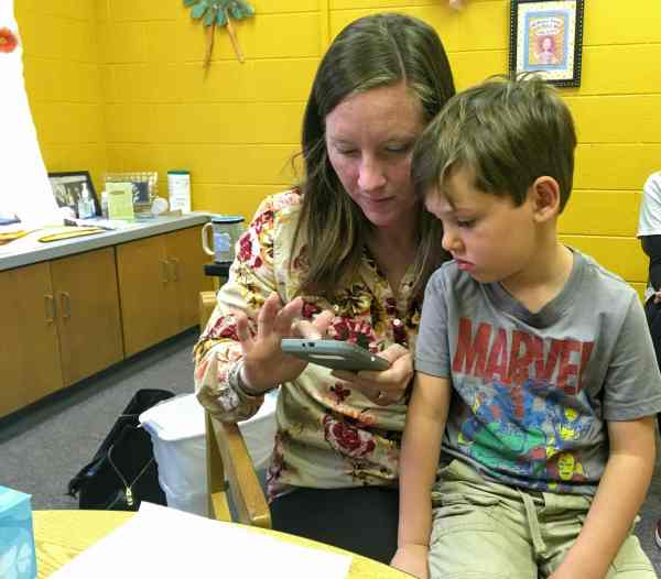 Brie and Atticus browse through photos of Baby Cow's adventures.