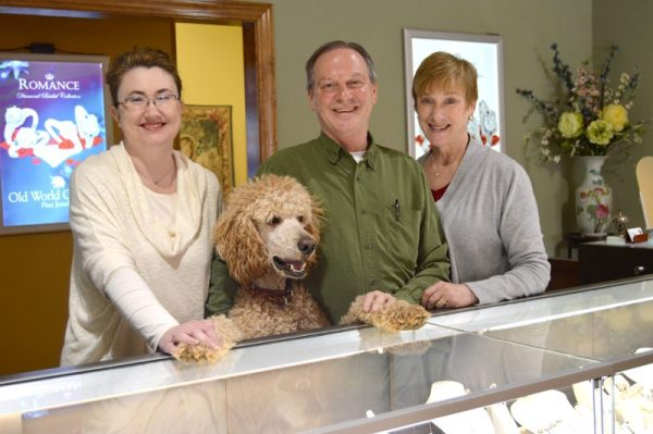 When you shop at Village Jewelers, you're bound to be greeted by smiling faces, maybe even those of Boone and Ozzie, Charlie and Joy's standard poodles, who are important fixtures in the store. Pictured here are Charlie, Joy and Boone with employee and friend Jennie Trivette.