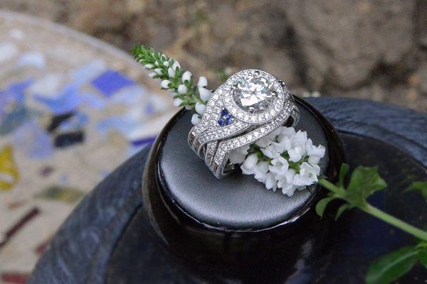 OWG helped create a new mounting for this diamond, which now features a diamond criss cross shank with a diamond halo and front and back diamond bands, as well as a trip of sapphires on each side for accent. Photo courtesy of Old World Galleries.