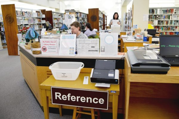 Employees of the Watauga Library work to help library patrons at the reference desk.