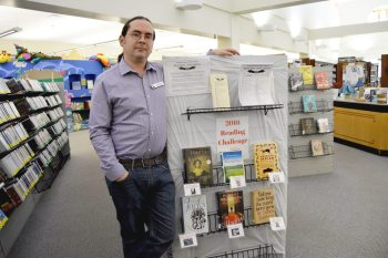 Darren Smith, a reference librarian in the adult services department, shows off a display for the 2016 Reading Challenge at the Watauga County Public Library.