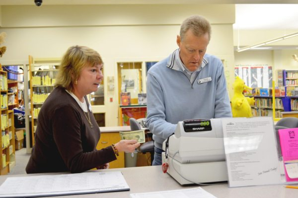 Circulation Assistant Lynn Presnell (left) and Circulation Manager Randy Feimster work together behind the circulation desk at the Watauga Library.