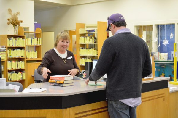 Circulation Assistant Lynn Presnell (left) helps a local reader check out new books for his family at the circulation desk in the Watauga Library.