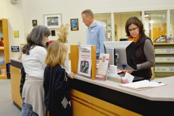 Employees at Watauga County Public Library help local patrons check out new books at the circulation desk. Pictured behind the desk are Circulation Manager Randy Feimster (left) and County Librarian Monica Caruso.