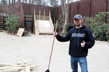 Danny Wilcox works to prepare for the amphitheater stage for the upcoming Daniel Boone Rail Jam.