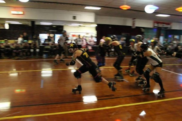 ARG jammer, PYT taking off while her teammates block Rogue Rollergirls Courtesy Kevin Gordon, ARG photographer