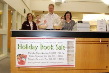 Randy Feimster (center) is pictured showing off gift baskets that are available at the Friends of the Library Holiday Book Sale this week in Boone. Also pictured are Monica Caruso and Angela Constantino. Photo by Ken Ketchie.