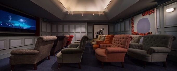 a dark room has a wall sized HD screen mounted on the wall that is playing a film, there are lots of big and brightly coloured arm chairs facing towards the screen