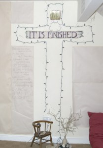 "A cross made of tree lights with the words ""It is finished"" in cross"
