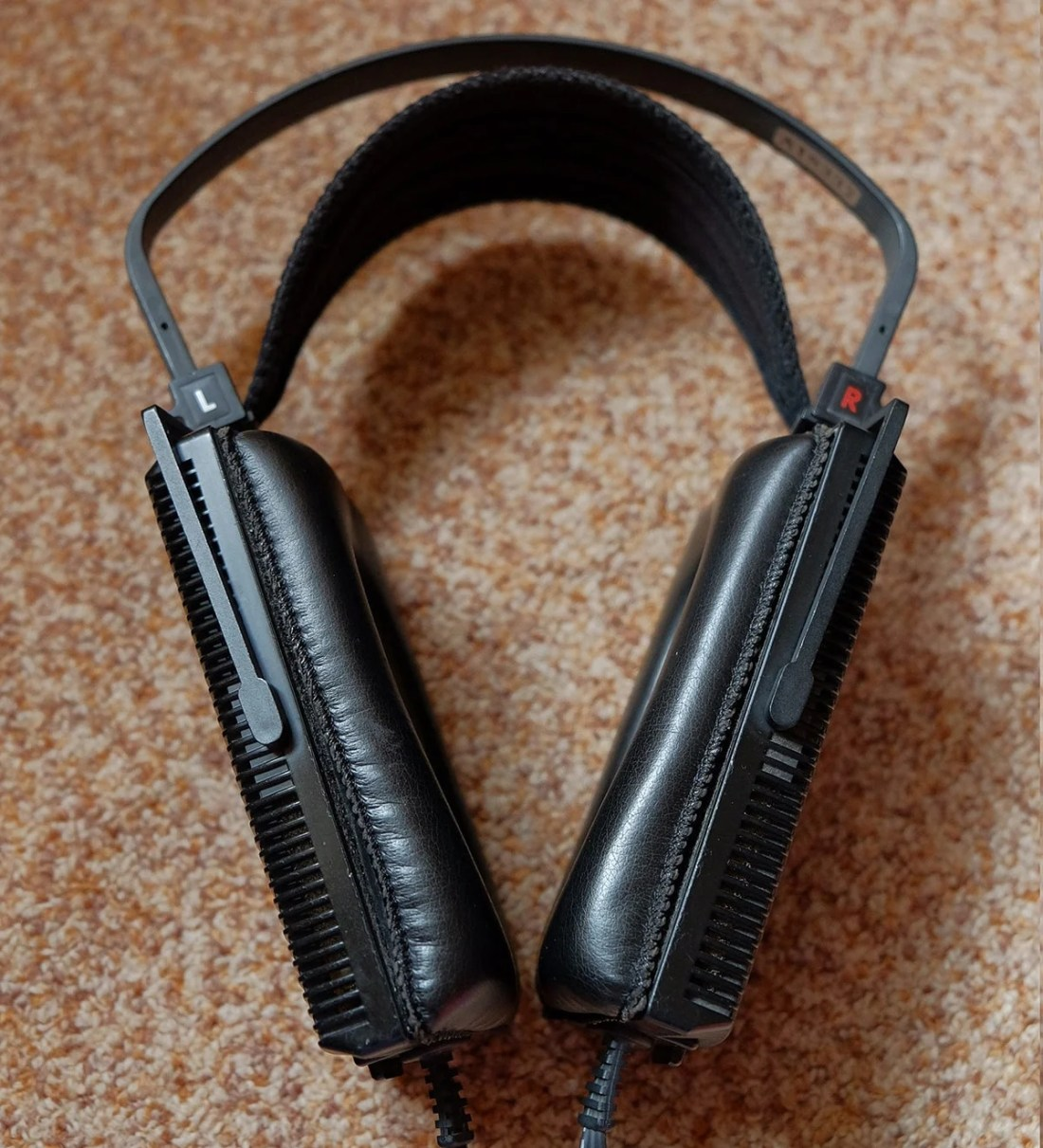 The pleather ear pads are thicker on the bottom to help for a better seal