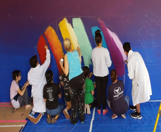 students painting the rainbow in the art mural project at Parkland