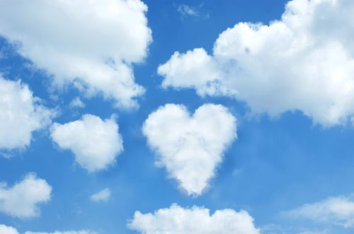 Sunny blue sky with a cloud in the shape of a heart