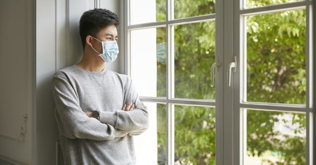 Young Asian man wearing mask inside the home.