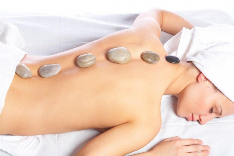 sleeping cute girl getting a stone massage in a spa