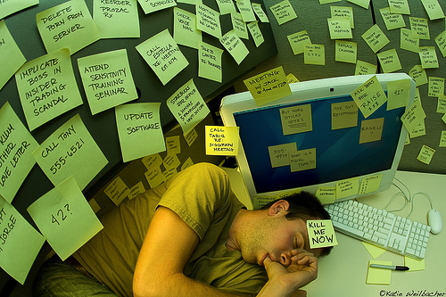 An image of lots of post it notes with a man asleep at the computer.