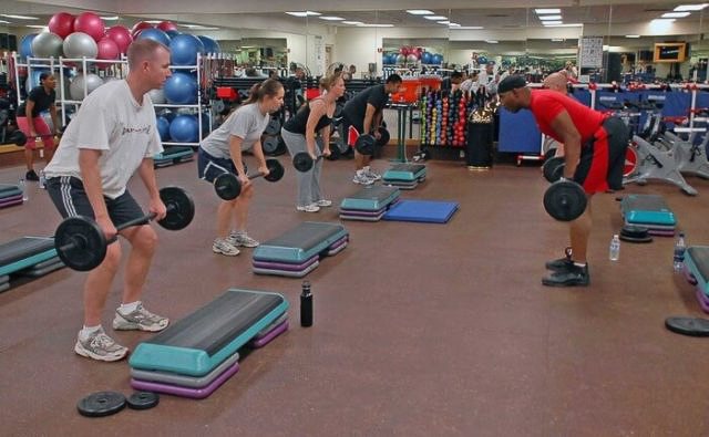 fitness instructor teaching gym members to use weights