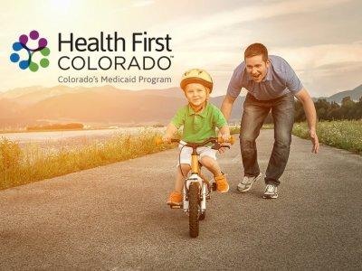 Health First Colorado - boy father bike with logo