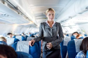 Smiling female cabin crew standing in an airplane and looking at the camera.