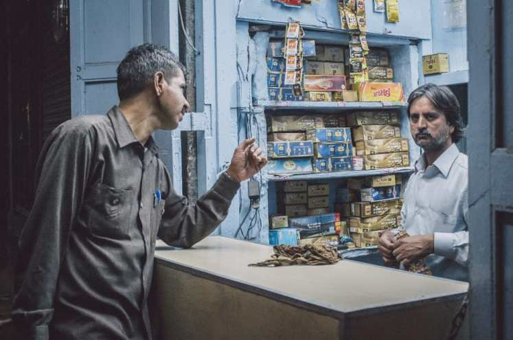 JODHPUR, INDIA - 16 FEBRUARY 2015: Indian vendor sells gutka to customer. Gutka has mild stimulant effect and is consumed by sucking and chewing. Post-processed with grain and texture.