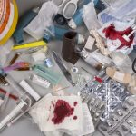 Hospital waste concept. Hazardous biomedical waste/ medical waste that needs to be carefully disposed of by incineration. Items include clinical waste such as used syringes and needles, used swabs, plasters and bandages. Used drug blister packs and ampules. Biomedical waste is potentially infectious. Image credit: Steve AllenUK / 123rf