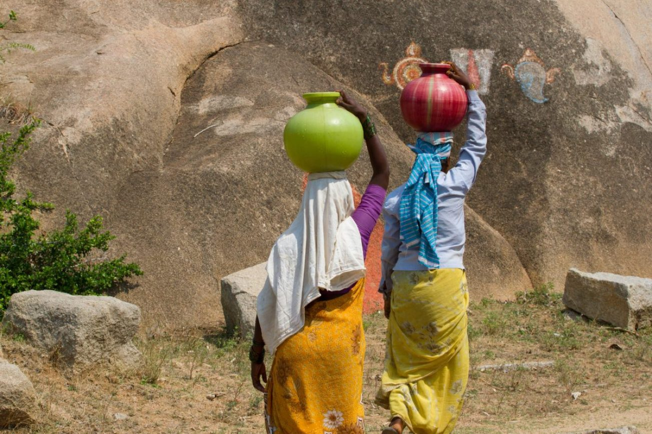 Two Indian women collect water for use in clay pots.