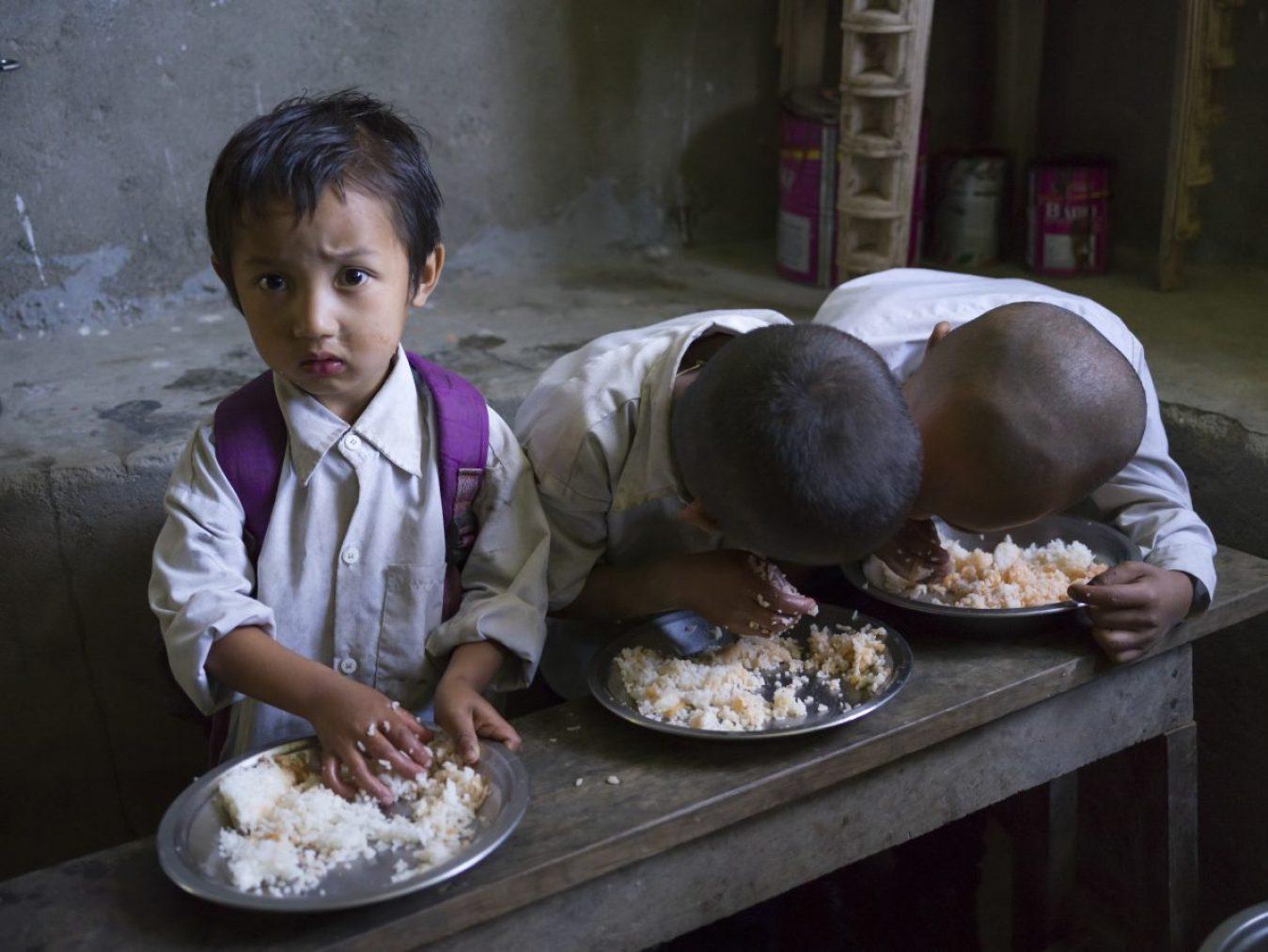 children. School children having mid-day meal in school, Radhu Khandu Village, Sikkim, India. Image credit: Keith Levit / 123rf. Hunger starvation concept.