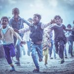 MATHURA, INDIA - Feburary 23,2018: Group of boisterous Indian children running for photograph in Agra, Uttar Pradesh, India.. Child health and wellbeing concept. Image credit: Sasin Tipchai / 123rf