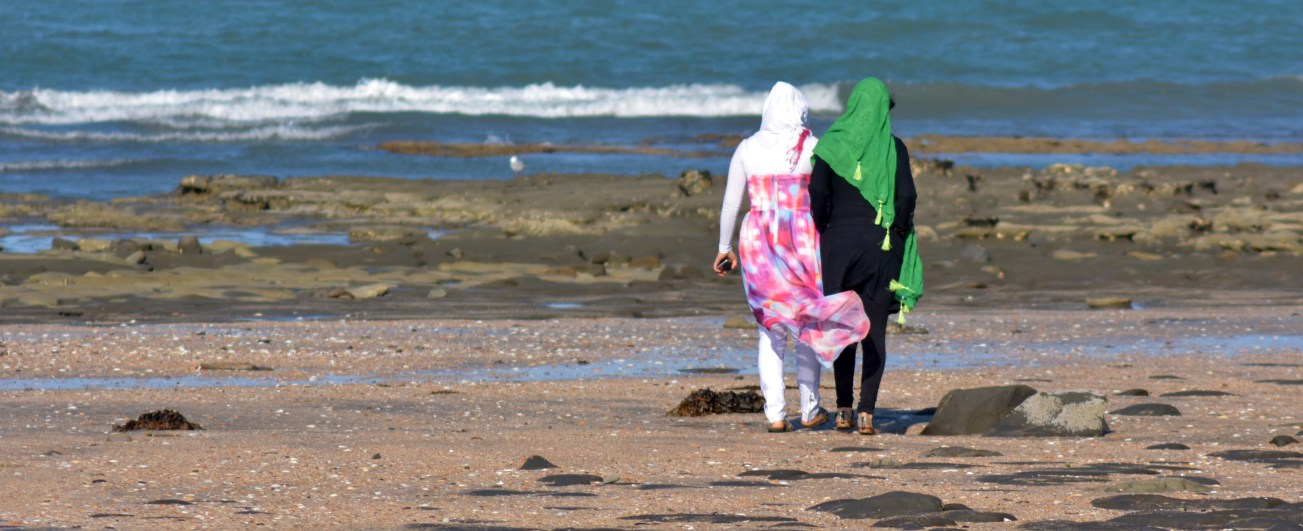 AUCKLAND, NZL - JAN 25 2015:Two muslim women on the beach.Over 130 million women and girls have experienced Female genital mutilation, 21% of Muslim girls and women have undergone female genital mutilation.