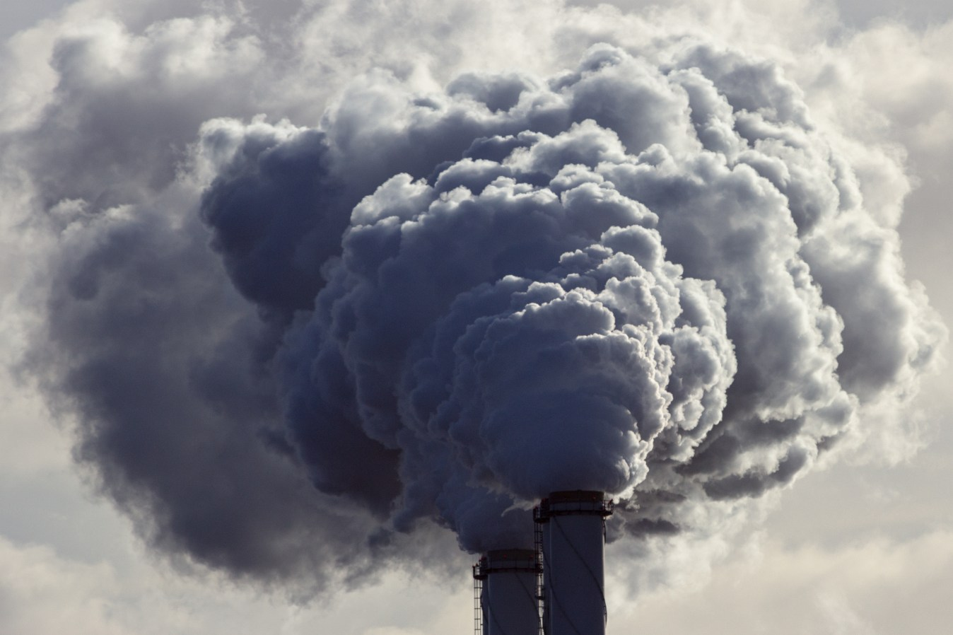 Air pollution from power plant chimneys. Toxic air concept. Mother Earth illustration. Image credit: jvdwolf / 123rf Climate crisis