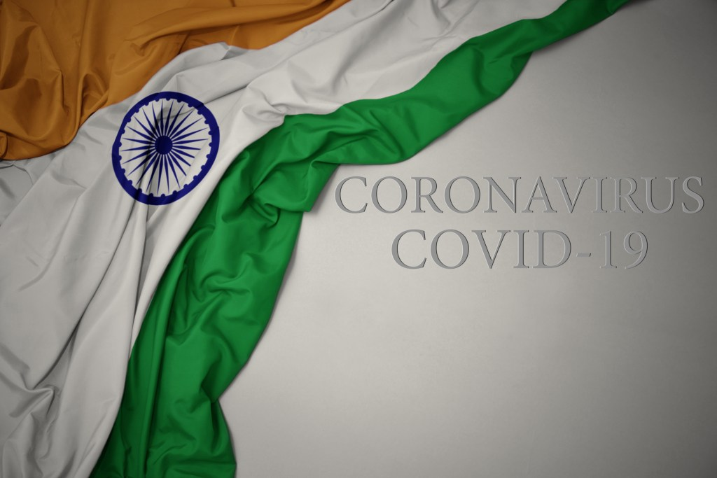 waving colorful national flag of india on a gray background with text coronavirus covid-19 . concept.. COVID-19 cases in India illustration. Indian COVID-19 cases concept. Cases of COVID-19 crisis in India concept. Image credit: luzitanija / 123rf. Used to illustrate one million deaths due to the pandemic.