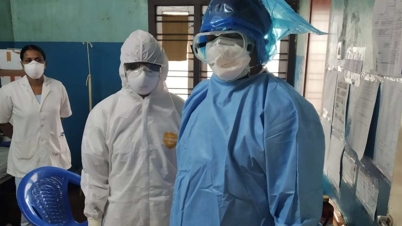 Health workers wearing personal protective equipment while caring for patients with coronavirus infection in the Indian state of Kerala. PPE shortages concept.
