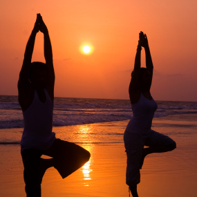 A couple doing yoga together on the beach during sunset.