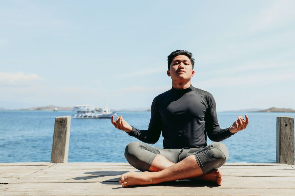Exercise Reduces Stress and Anxiety - Man Exercising Yoga on Beach