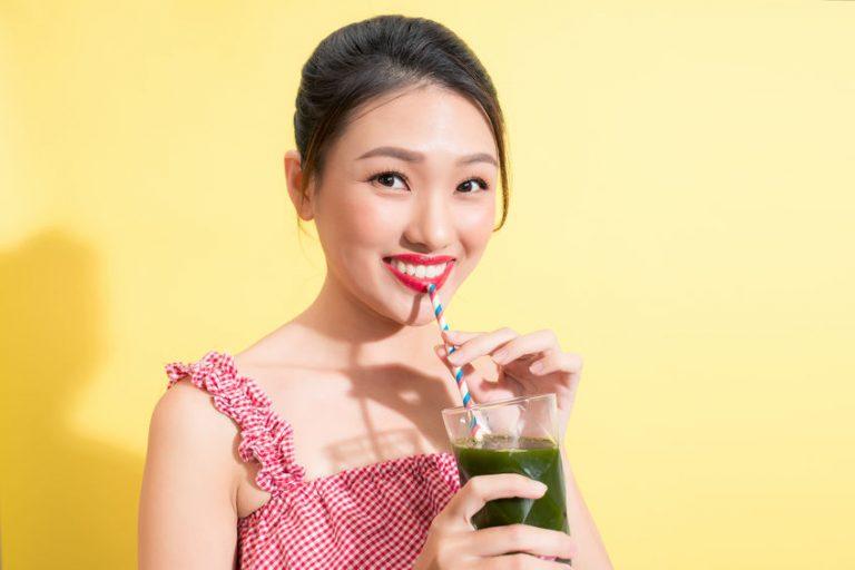 Donna che beve un succo di wheatgrass
