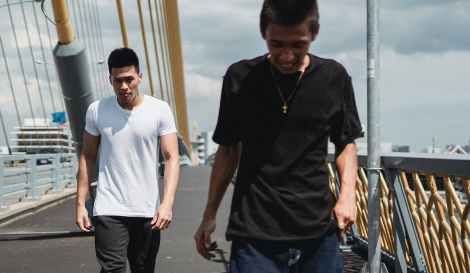 young asian men walking on asphalt bridge