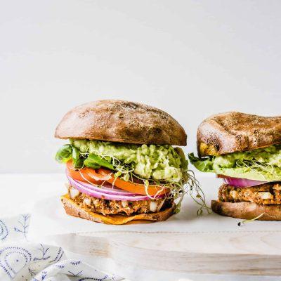 Vegan, gluten-free, plant-based BBQ burger on a sweet potato bun with guacamole, tomato, onion, lettuce, sprouts