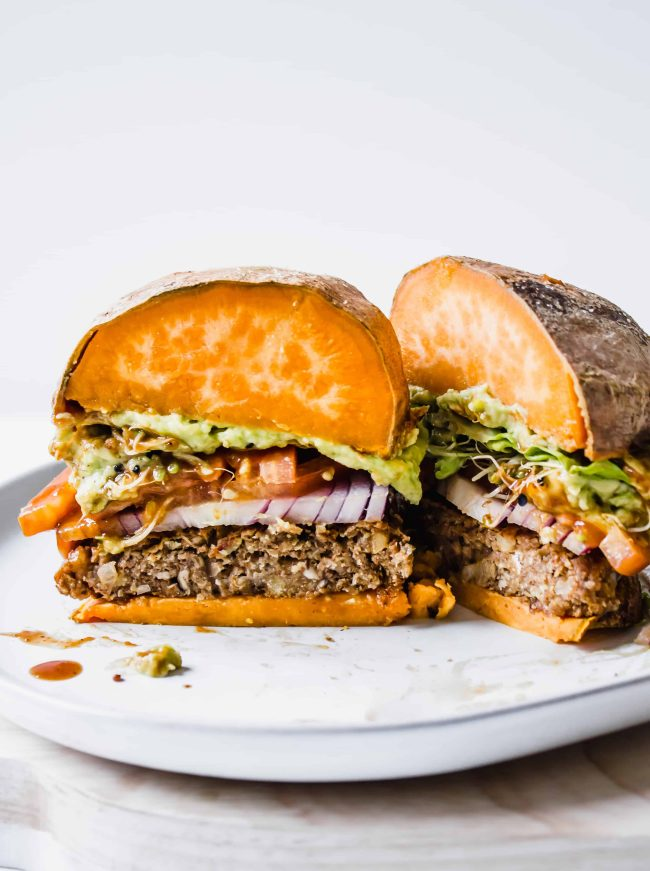 Vegan, gluten-free, plant-based BBQ burger on a sweet potato bun with guacamole, tomato, onion, lettuce, sprouts
