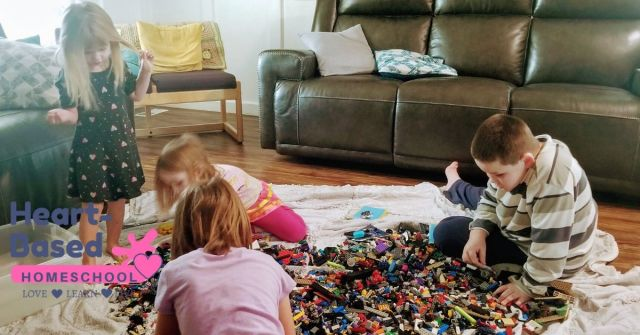 Kids playing with Lego on a blanket during morning time.