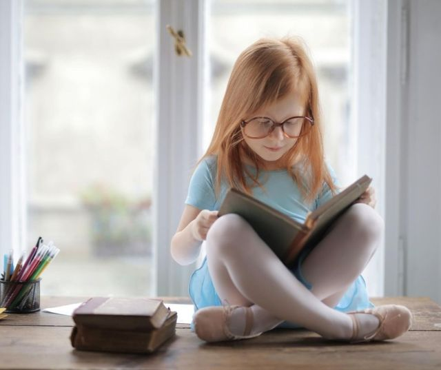 Young girl sitting on a tabletop reading a book.