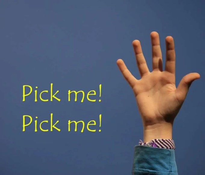 Child's raised hand against blue sky with the words pick me, pick me.