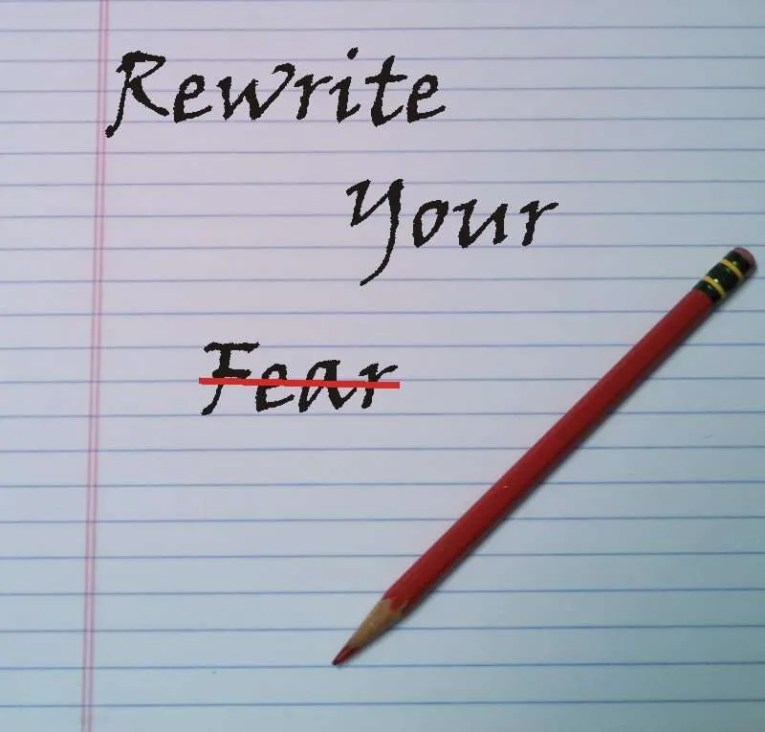 Notepad and pencil with the words Rewrite Your Fear, with the word fear crossed out with a red line.