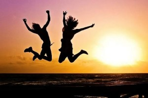 Two people jumping joyfully in the air silhouetted against the setting sun.