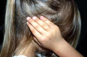 A little girl in profile with her ears covered with her hands.