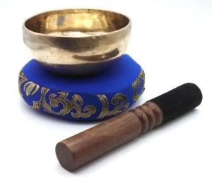 Tibetan singing bowl with wooden mallet and cushion.