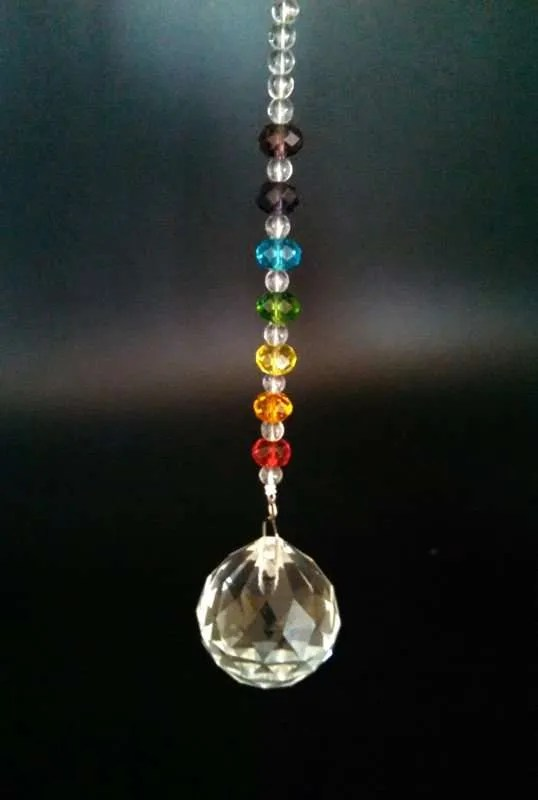 Hanging faceted crystal with chakra colored crystals along chain.