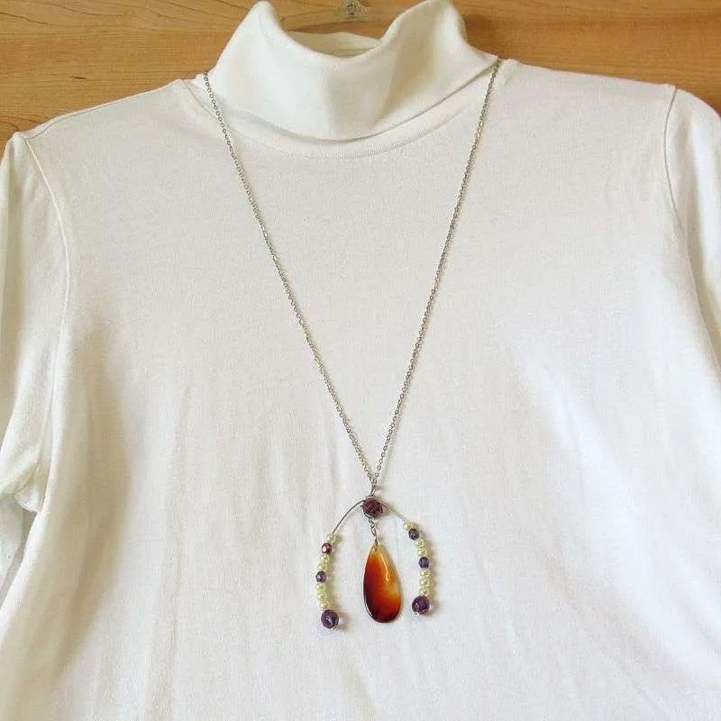 Red agate teardrop pendant with beaded horseshoe embellishment