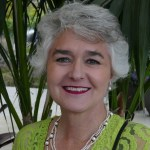 Melanie Trethowan - head and shoulders photo. Lime green shirt, pearls and grey hair