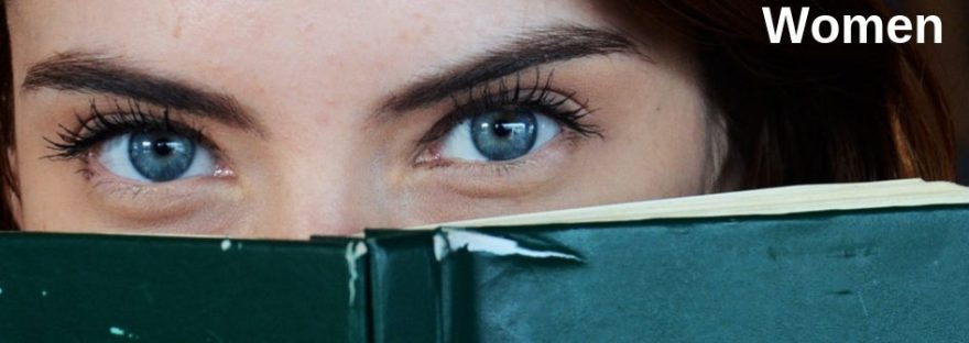 A woman peering over the edge of a book