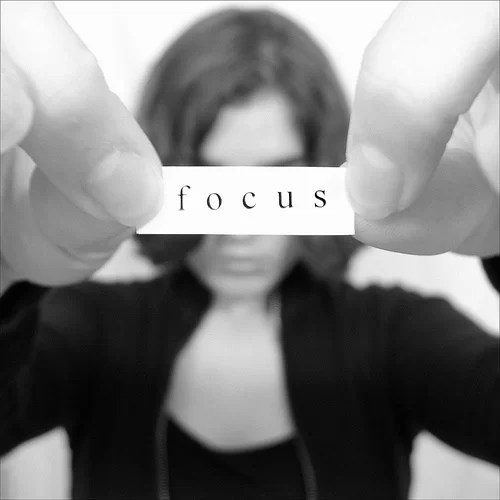 A woman holds a note that says 'focus'