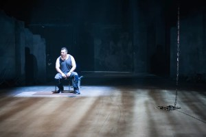 A man sits in an empty room, ominously lit